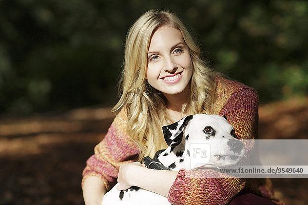 Porträt einer lächelnden blonden Frau mit Dalmatinerin