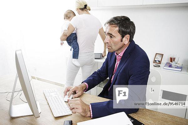 Geschäftsmann  der von zu Hause aus arbeitet  Frau und Kind im Hintergrund