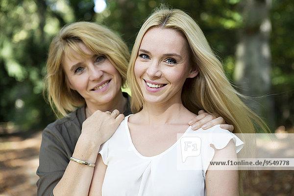 Porträt der lächelnden Mutter und erwachsenen Tochter im Park