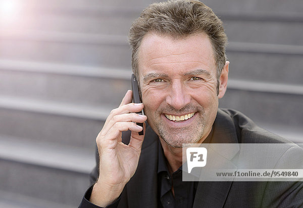 Portrait of smiling businessman sitting on steps telephoning with smartphone