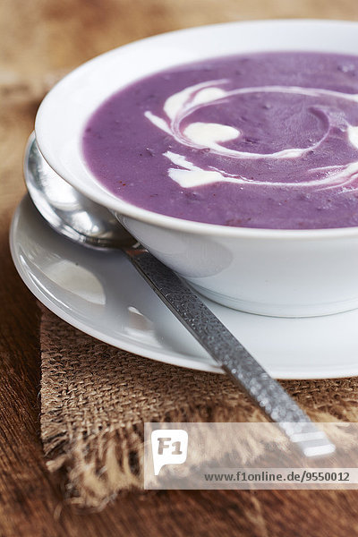 Violette Kartoffel-Lauch-Suppe mit einem Strudel Soja-Joghurt