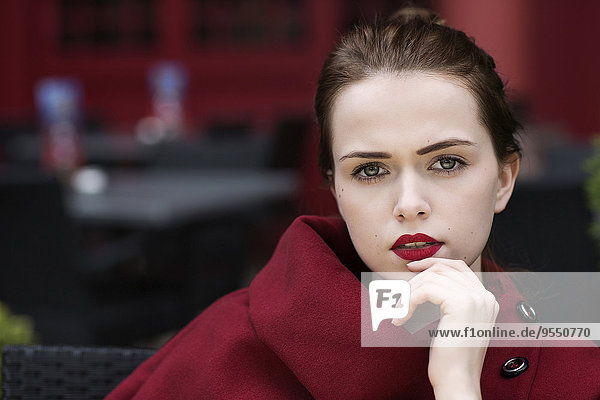 Portrait of young woman with red lips wearing red cape