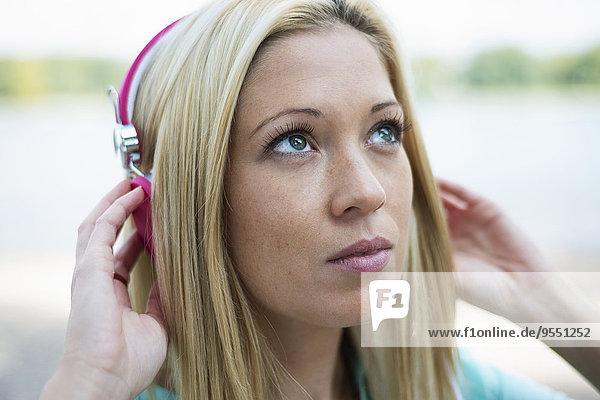 Porträt einer jungen Frau mit Kopfhörer nach oben schauend