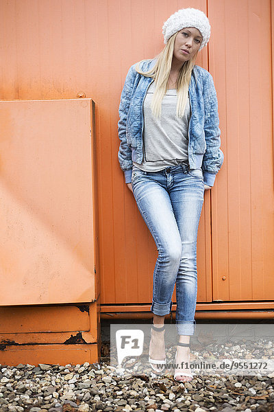 Fashionable blond young woman leaning at orange facade