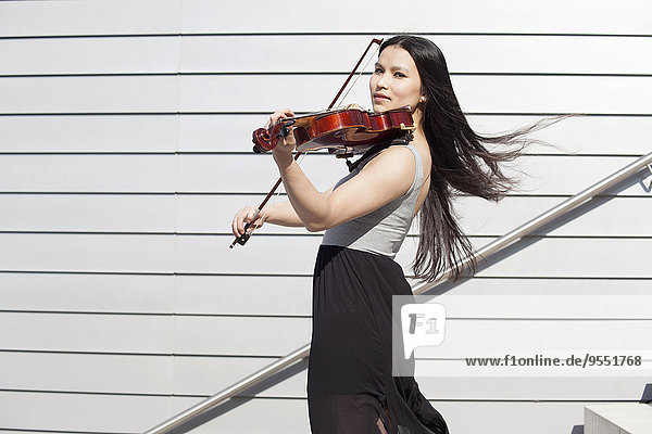 Portrait of young female Asian playing violin on stairs