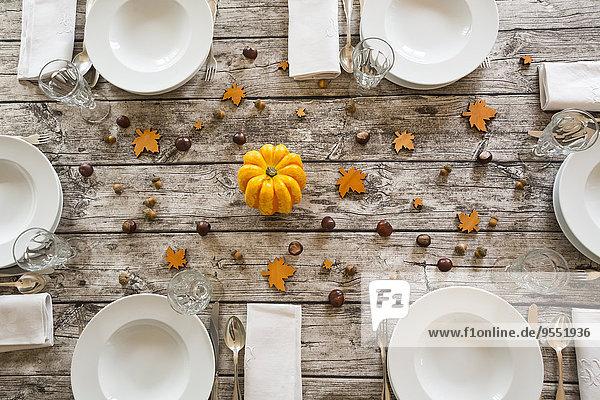 Herbstlich gedeckter Tisch mit gelbem Kürbis  Kastanien und Eicheln