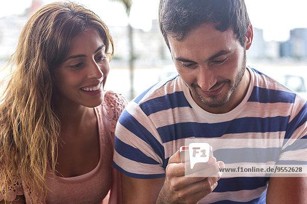 Junges Paar sendet Nachrichten mit einem Smartphone