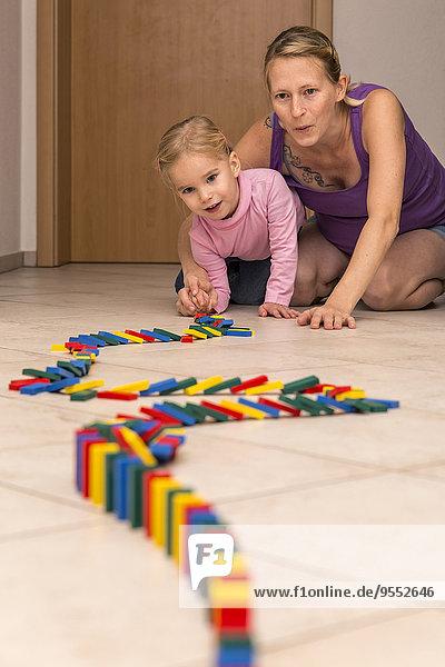 Mutter und Tochter mit Dominoreihe