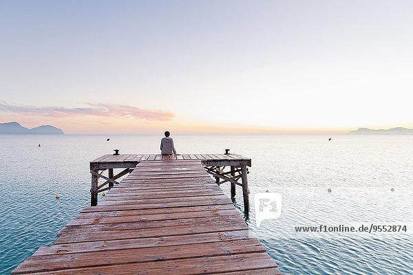 Spanien  Balearen  Mallorca  ein Teenager sitzt morgens auf einem Steg.