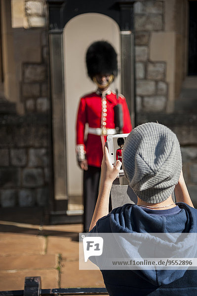 UK  London  Junge fotografiert Wache vor dem Tower of London mit seinem digitalen Tablett