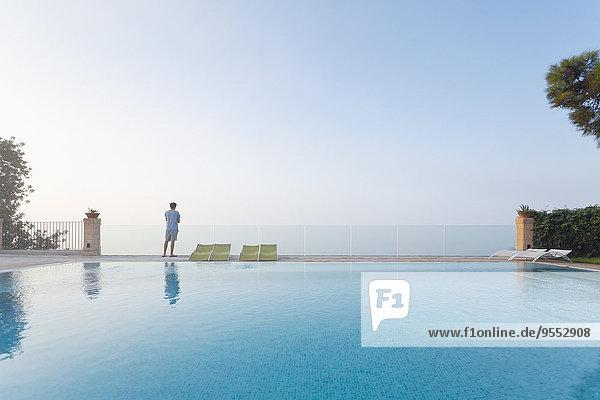 Spanien  Balearen  Mallorca  ein Teenager steht auf einer Glasschiene am Swimmingpool.