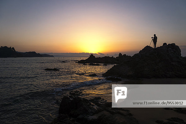 Spanien  Katalonien  Lloret de Mar  Platja de Santa Christina  Silhouette eines Fotografen bei Sonnenaufgang