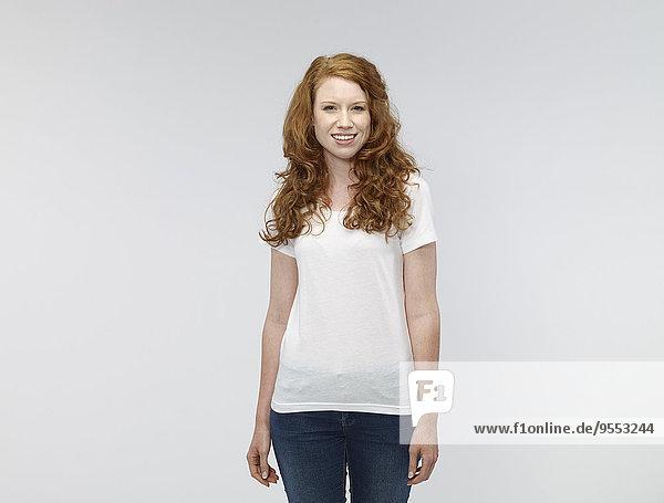 Porträt einer lächelnden jungen Frau vor weißem Hintergrund