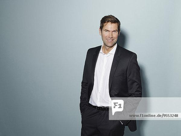 Porträt eines lächelnden Geschäftsmannes in schwarzem Anzug und weißem Hemd