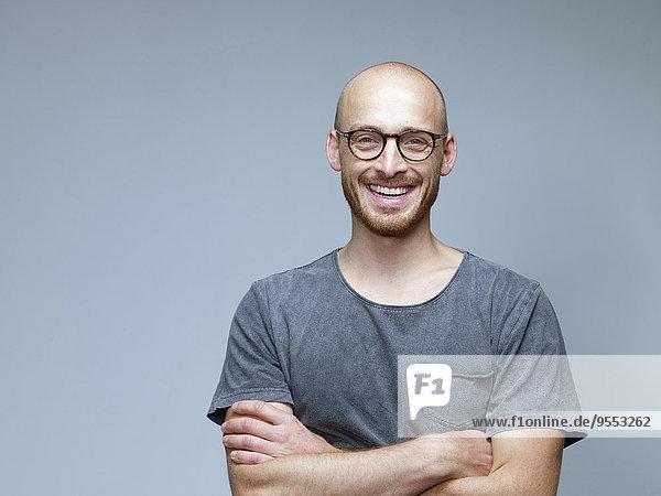 Porträt eines lächelnden Mannes mit gekreuzten Armen vor grauem Hintergrund