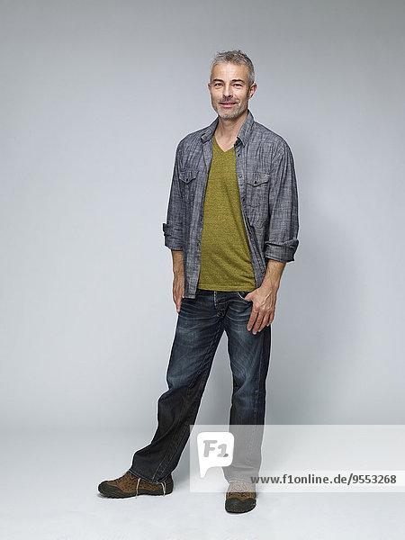Porträt eines reifen Mannes mit der Hand in der Tasche vor grauem Hintergrund