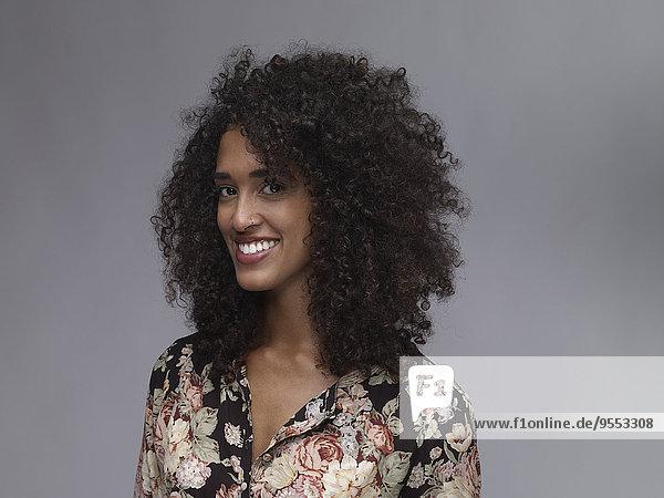 Porträt einer lächelnden jungen Frau mit Nasenring und Afro vor grauem Hintergrund