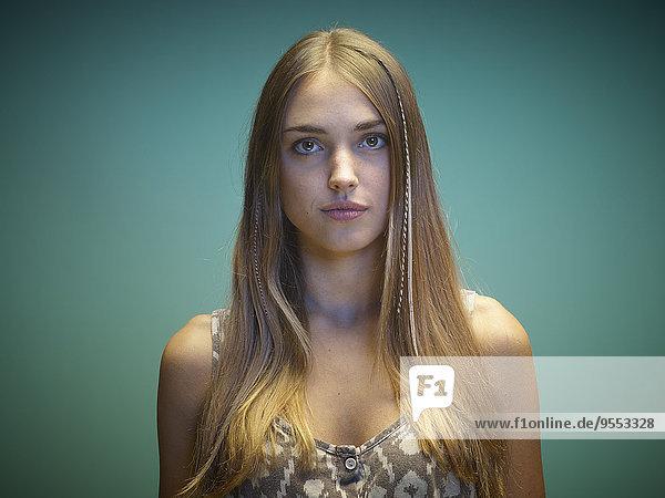 Porträt einer jungen Frau vor grünem Hintergrund