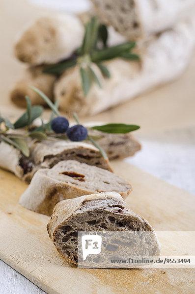 Geschnittenes hausgemachtes Baguette mit Oliven und getrockneten Tomaten auf Holzplatte
