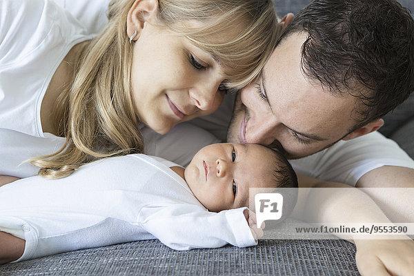 Junges Paar mit neugeborenem Jungen zu Hause