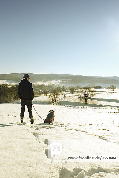 Germany  Bergisches Land  man walking dog in winter landscape