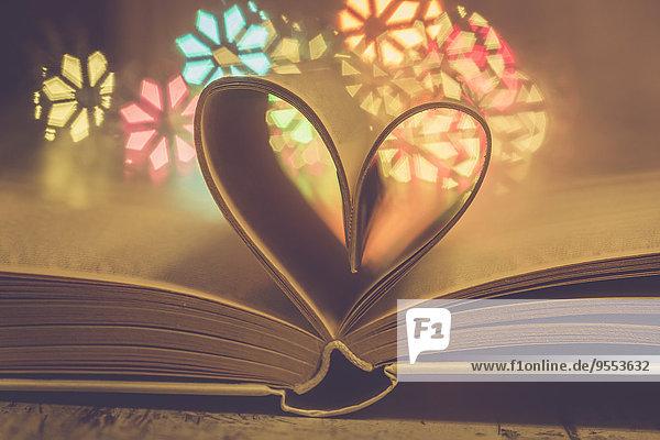 Herzförmige Buchseiten vor bunten Lichtern