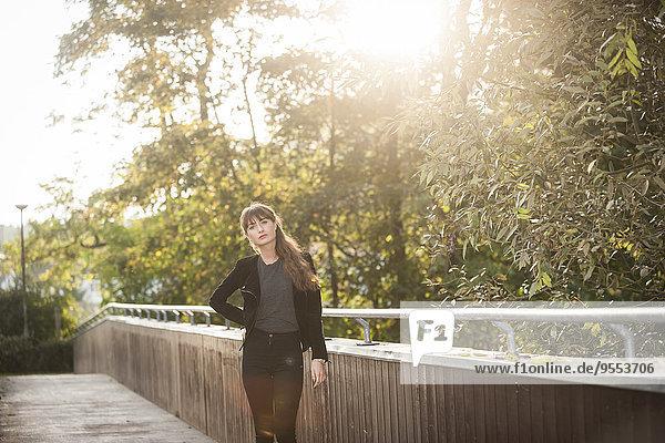 Ernsthaft aussehende junge Frau auf einem Steg im Gegenlicht stehend