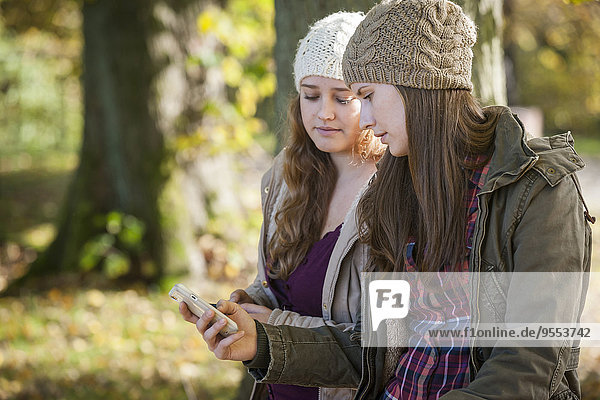 Deutschland  Rheinland-Pfalz  Studentinnen mit Smartphone im Außenbereich
