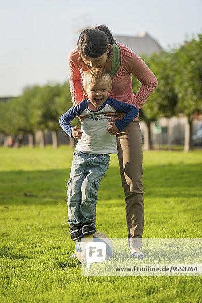 Mutter und Sohn mit Ball auf der Wiese
