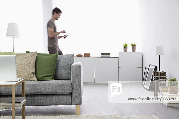 Junger Mann mit digitalem Tablett im Wohnzimmer