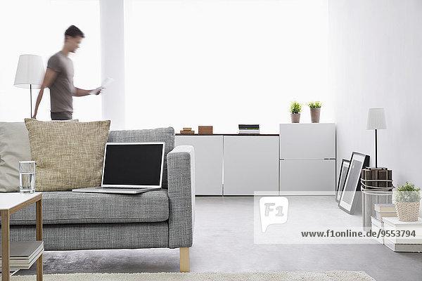 Geöffneter Laptop auf der Couch im modernen Wohnzimmer