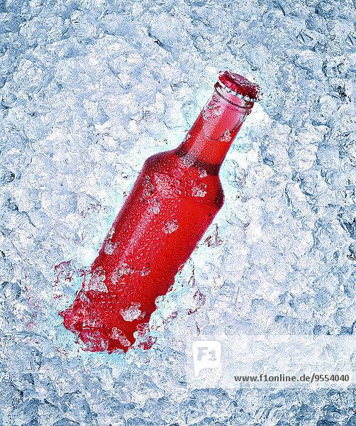 Glasflasche mit rotem Getränk auf Crushed Ice
