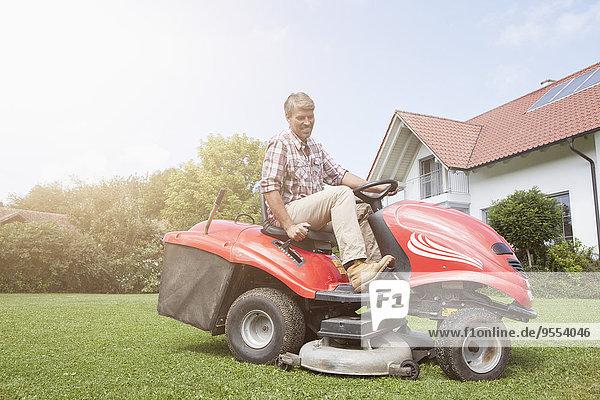 Mann auf Rasenmäher im Garten