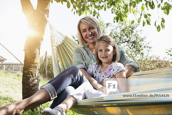 Glückliche Mutter und Tochter in der Hängematte sitzend