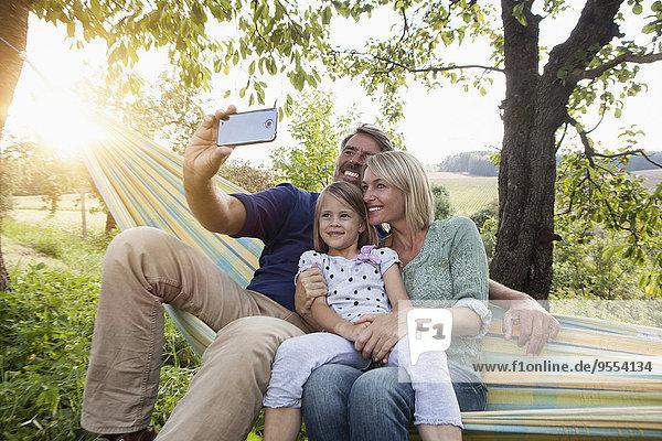Glückliche Familie  die Selfie in der Hängematte nimmt