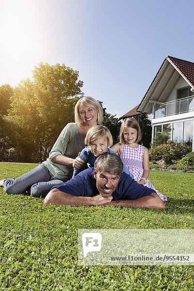 Glückliche Familie auf dem Rasen im Garten liegend