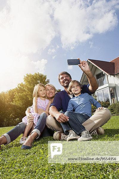 Glückliche Familie nimmt Selfie im Garten auf