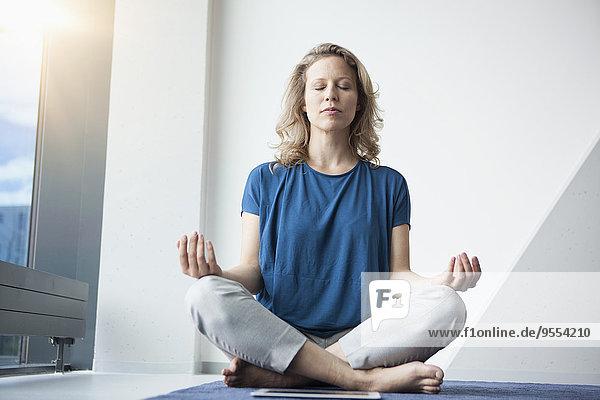 Reife Frau beim Yoga zu Hause