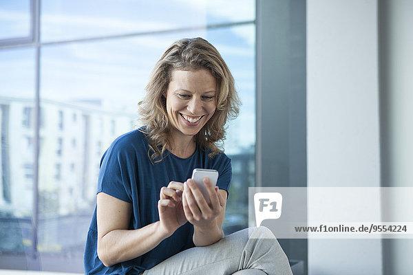 Lächelnde reife Frau mit ihrem Smartphone zu Hause
