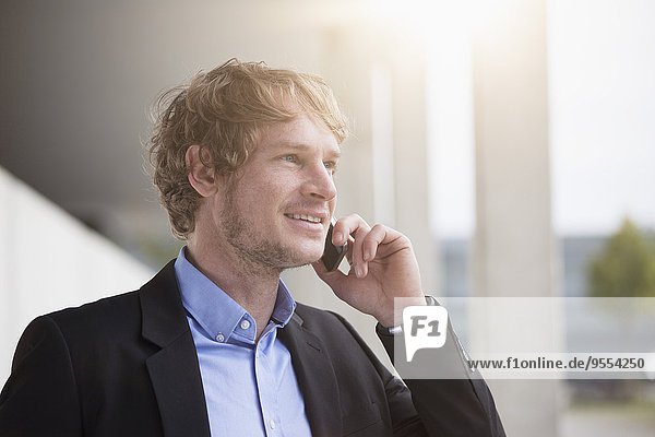 Portrait of smiling businessman telephoning with smartphone