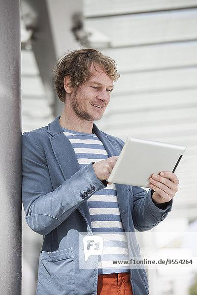 Porträt eines lächelnden Mannes mit digitalem Tablett