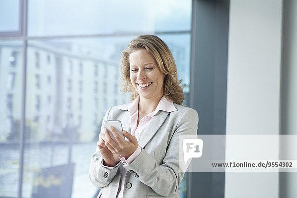 Lächelnde Geschäftsfrau mit Handy im Büro