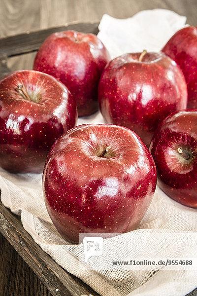 Rote Äpfel auf Vlies und Holztablett