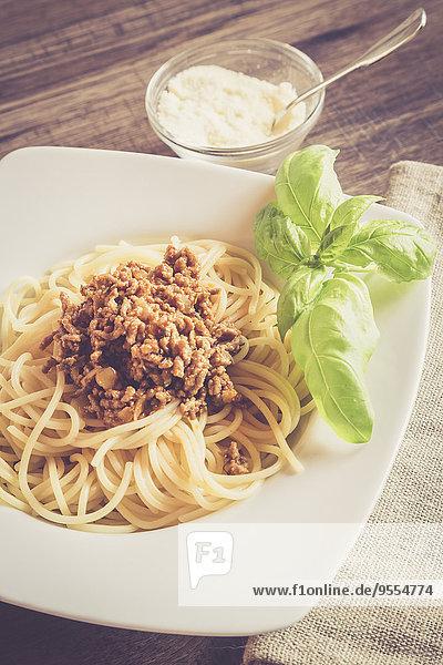 Spaghetti mit Bolognesesauce  Basilikum und Parmesan auf dem Teller