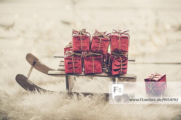 Miniaturschlitten mit kleinen roten Weihnachtsgeschenkboxen