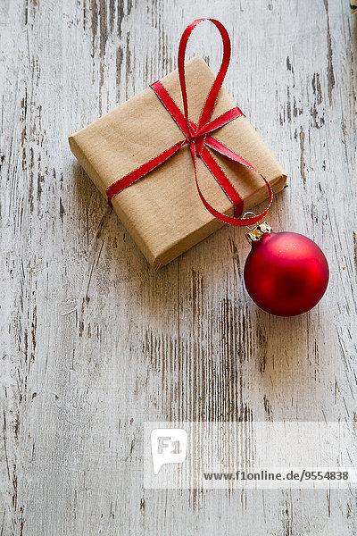 Weihnachtsgeschenk mit roter Weihnachtskugel auf Holz