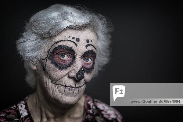 Porträt einer älteren Frau mit Zuckerschädel-Make-up vor schwarzem Hintergrund
