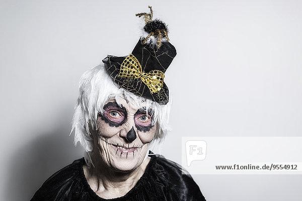 Porträt einer älteren Frau mit Zucker-Schädel-Make-up und Zierhut