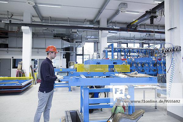 Junge Techniker  die in einer Industriehalle arbeiten