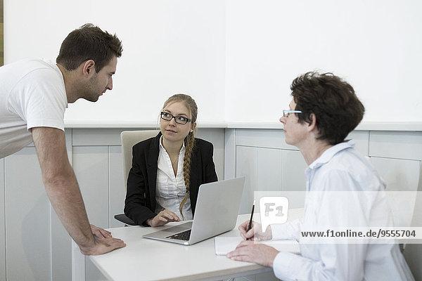 Drei Personen im Büro mit Laptop und Schreibblock